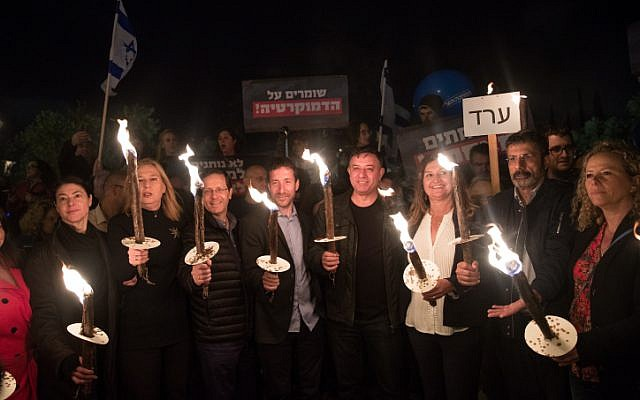 Leader of the Zionist Union party Avi Gabbay and Zionist Union MKs hold torches at a protest against attempts to enact laws that bypass the High Court of Justice and public criticism of the court's intervention in the legislative process, in Jerusalem, on  April 21, 2018. (Yonatan Sindel/Flash90)