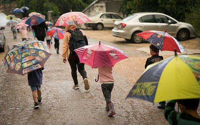 Kids take cover under umbrellas on a rainy day in Kibbutz Sarid in northern Israel, April 25, 2018. (Anat Hermony/Flash90)
