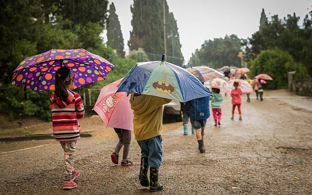 Kids take cover under umbrellas on a rainy day as they walk in Kibbutz Sarid in northern Israel on April 25, 2018. (Anat Hermony/Flash90)