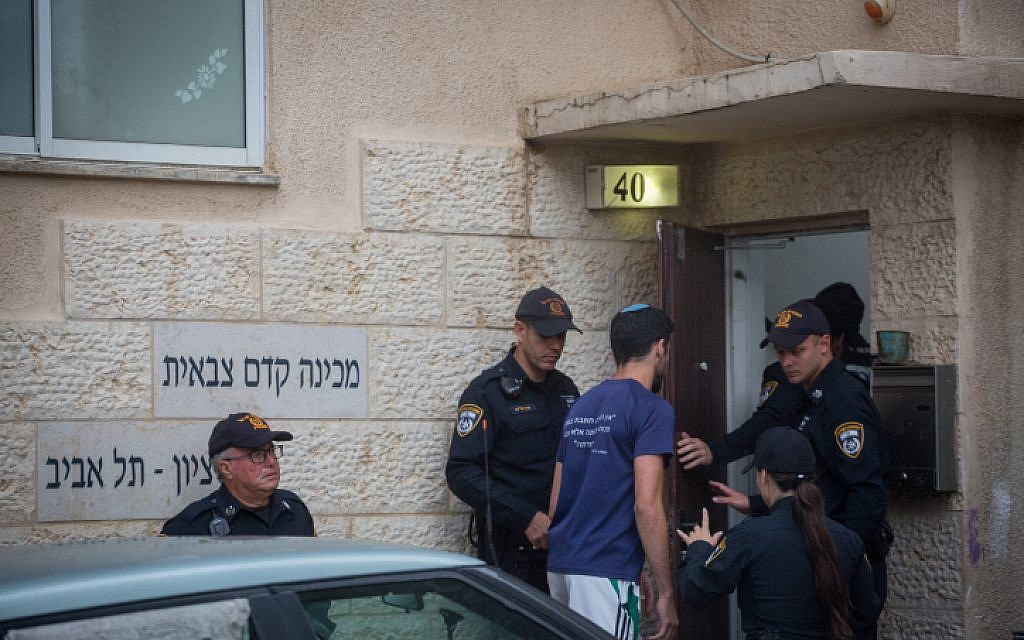 Police stand outside the Bnei Tzion pre-army academy in Tel Aviv, from which 9 students were killed in a flash flood in the Judean desert, on April 26, 2018. (Miriam Alster/Flash90)