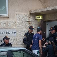 Police stand outside the Benny Tzion pre-army academy in Tel Aviv, from which 10 students were killed in a flash flood in the Judean Desert, on April 26, 2018. (Miriam Alster/Flash90)