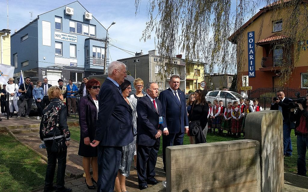 From left: Limmud FSU co-founder Chaim Chessler, deputy chair of March of the Living Aharon Tamir, and Mayor Andrzej Pietrasik lay wreaths at the onetime home and birthplace of first Israeli prime minister David Ben-Gurion in Plonsk, Poland, April 15, 2018. (Yaakov Schwartz/Times of Israel)