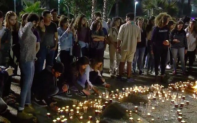 Israeli teens light candles at a vigil at Tel Aviv's Rabin Square on April 28, 2018, in memory of the 10 victims killed in a flash flood while hiking in the Judean Desert. (Screen capture/YouTube)