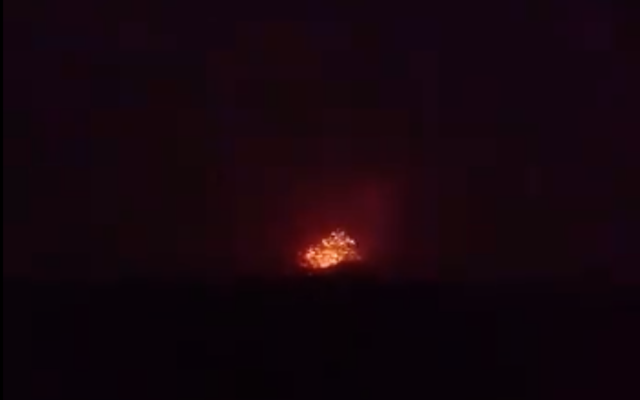 An explosion is seen coming from an army base, allegedly used by Iran-backed militias, outside the northern Syria city of Hama on April 29, 2018. (Screen capture; Facebook)