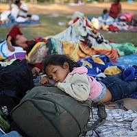 "Nayeli Zelaya, from El Salvador, rests alongside her two sleeping siblings, at the sports club where Central American migrants traveling with the annual ""Stations of the Cross"" caravan are camped out in Mexico, April 4, 2018. (AP Photo/Felix Marquez)"