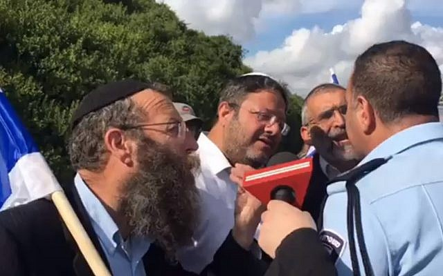 From L to R: Far-right activists Baruch Marzel, Itamar Ben Gvir and Michael Ben Ari confront a police officer who prevented them from attending an anti-mosque protest in Umm al-Fahm on April 10, 2017. (Channel 2 screenshot)