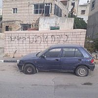 Graffiti found spray-painted on a wall next to a car whose tires were slashed in the Palestinian village of Deir Ammar, near Qalqilya on April 25, 2018. (Israel Police