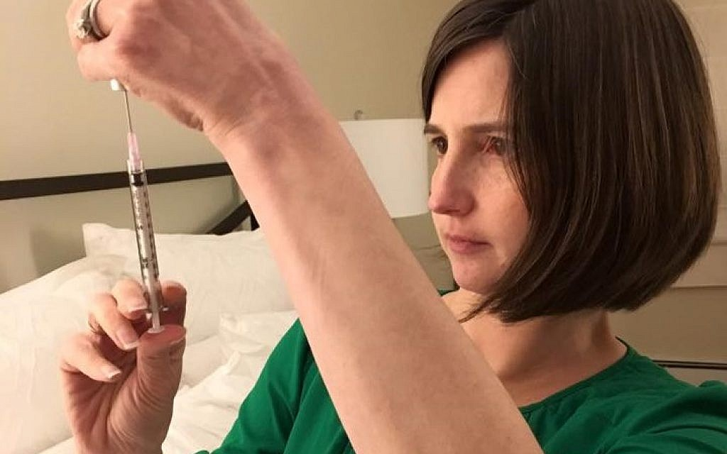 Carrie Bornstein of Boston prepares for an injection during her surrogate pregnancy for a British-Jewish couple living in London, 2017 (courtesy)