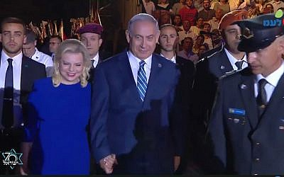 Prime Minister Benjamin Netanyahu (R) and his wife Sara arrive at the torch lighting ceremony at Mount Herzl on April 18, 2018. (Screen capture/Facebook)