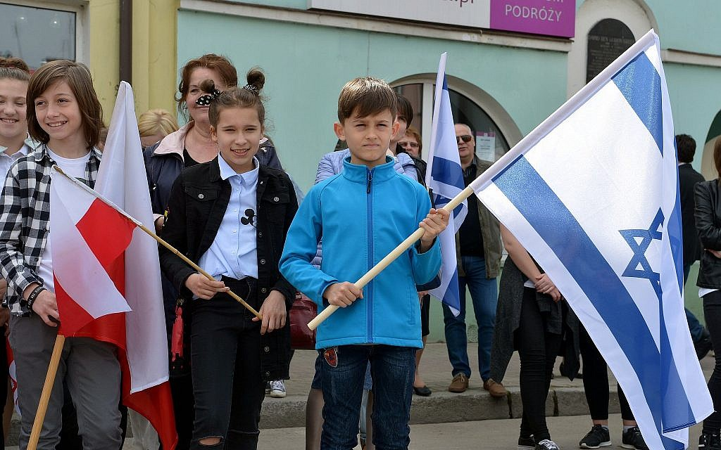 Local children hold Polish and Israeli flags in Plonsk, Poland, the birthplace of first Israeli prime minister David Ben-Gurion, in celebration of Israel's 70 years of independence, April 15, 2018.  (Yossi Zeliger/Limmud FSU)