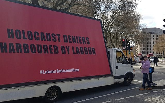 Keith Walker engaging the driver of a van transporting a billboard about anti-Semitism in the Labour Party on London's Parliament Square, April 17, 2018. (Cnaan Liphshiz/JTA)