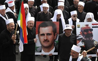 Druze residents of the Ein Qiniye village on the Israeli side of the Golan Heights hold pictures of the Syrian president Bashar Assad and Issam Zahreddine, the late Major General of the Syrian Republican Guard as they march during a rally marking Syria's Independence Day on April 17, 2018. (AFP PHOTO / JALAA MAREY)