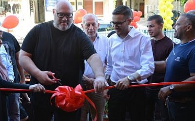 Restauranteur Moshik Roth (left) cuts the ribbon on his latest branch of Eight, his chain of eight-shekel restaurants, now in Baka Al Garbiya (Courtesy Eight)
