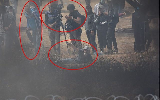 A Photograph released by the IDF shows a Palestinian protester (bottom) trying to place an explosive device on the fence. Near him are two journalists (center) and a man crutches (IDF spokesperson)