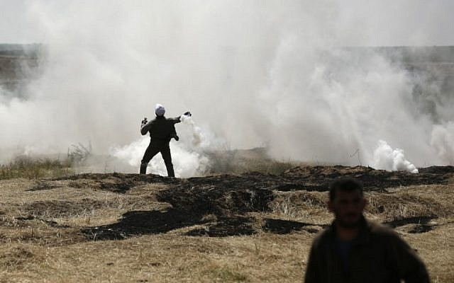 A Palestinian man throws a tear gas canister at the Israel-Gaza border during a protest, east of Gaza City in the Gaza Strip, on April 6, 2018.  (AFP PHOTO / MAHMUD HAMS)