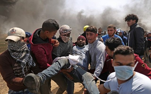 Palestinian men carry an injured protester after clashes with Israeli forces at the Israel-Gaza border during a protest, east of Gaza City in the Gaza Strip, on April 6, 2018. (AFP PHOTO / MAHMUD HAMS)