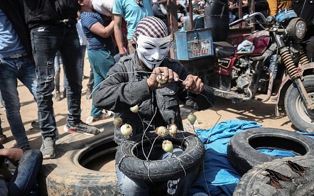 A Palestinian man wearing mask threads onions onto a wire to reduce the effects of tear gas during protests at the Israel-Gaza border near Khan Yunis, east of Gaza City, on April 6, 2018.  (AFP PHOTO / SAID KHATIB)