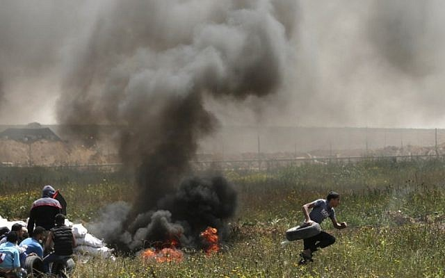 Palestinian men burn tires to use the smoke to protect themselves from Israeli soldiers close to the Israel-Gaza border during a protest, east of Gaza City in the Gaza Strip, on April 6, 2018.  (AFP PHOTO / MAHMUD HAMS)