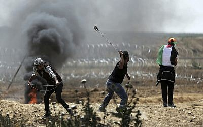 Palestinian protesters hurl stones at Israeli troops during a protest at the Gaza Strip's border with Israel, Friday, April 13, 2018. (AP Photo/Khalil Hamra)