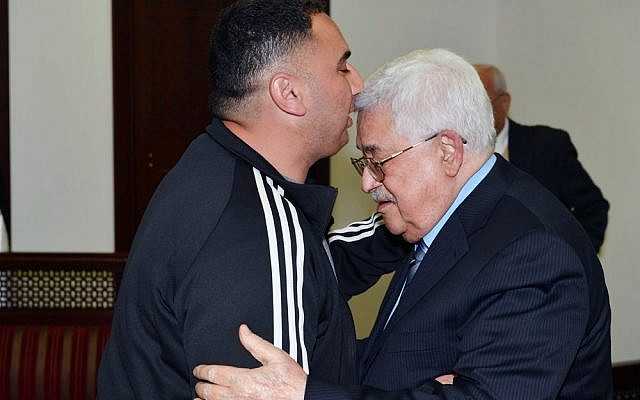 Palestinian Authority President Mahmoud Abbas (r), welcomes Rajaei Haddad, who spent 20 years in the Israeli prisons for his involvement in a 1997 terror attack which killed Gabriel Hirschberg. (WAFA/Thaer Ghanaim)