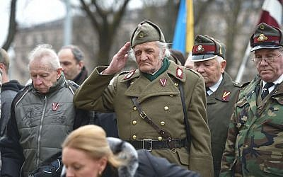 A man dressed in a pre-WWII Latvian military uniform salutes as veterans of the Latvian Legion, a force that was commanded by the German Nazi Waffen SS during WWII, and their sympathizers  walk to the Monument of Freedom in Riga, Latvia on March 16, 2016. (Ilmars Znotins/AFP/Getty Images/via JTA)