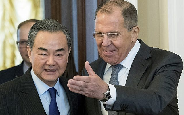 Russian Foreign Minister Sergey Lavrov, right, and China's Foreign Minister Wang Yi enter a hall during their meeting in Moscow, Russia, April 5, 2018. (AP Photo/Pavel Golovkin)