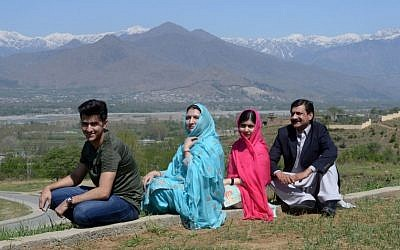 Pakistani activist and Nobel Peace Prize laureate Malala Yousafzai (2R) poses for a photograph along with her father Ziauddin Yousafzai (R), mother Torpekai (2L) and brother Atal Yousafzai (L), at the all-boys Swat Cadet College Guli Bagh some 15 kilometers outside of the family's hometown of Mingora, March 31, 2018. (AFP PHOTO / ABDUL MAJEED)