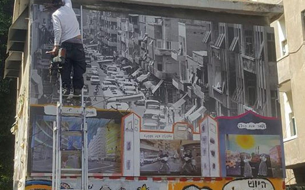 A municipality worker installs a temporary historical photo over a mural depicting the murder of Yitzhak Rabin, in Tel Aviv on April 16, 2018. (courtesy Facebook)