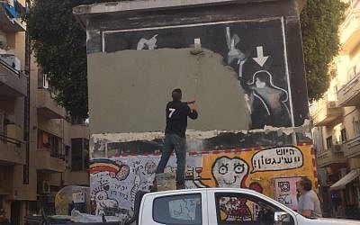 A municipality worker paints over Yigal Shtayim's mural depicting the murder of Rabin in Tel Aviv on April 17, 2018. (courtesy Facebook)