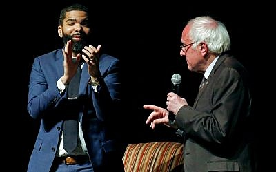 In this April 4, 2018 photo, Jackson Mayor Chokwe Antar Lumumba, left, applauds as US Sen. Bernie Sanders, I-Vt., answers a question during a town hall meeting examining economic justice 50 years after the assassination of Dr. Martin Luther King Jr., in Jackson, Miss. (AP Photo/Rogelio V. Solis)