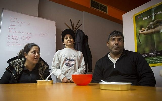 Ramin Lovimi, a refugee from Iran,  his wife Shahla Lovimi and their daughter Asma Lovimi are pictured during an interview with AFP at a migrant center in Belgrade on March 14, 2018. (AFP PHOTO / OLIVER BUNIC)