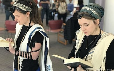 Rabbinical students at Hebrew College near Boston, including Gita Karasov, left, are creating a video that shows women, transgender and non-binary Jews demonstrating how to wear tefillin. (Dena Trugman/via JTA)