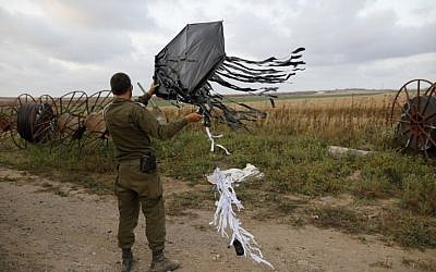An Israeli soldier holds a kite flown over the border from Gaza in a tactic recently used by Palestinian protesters to start fires in Israeli  on the Israel-Gaza border near the kibbutz of Kfar Aza on April 24, 2018. (AFP PHOTO / Menahem KAHANA)