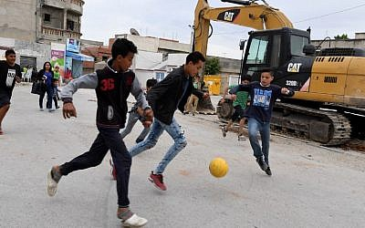 Children play football in the streets of Ettadhamen city on April 30, 2018, an impoverished area of Greater Tunis. (AFP/ FETHI BELAID)