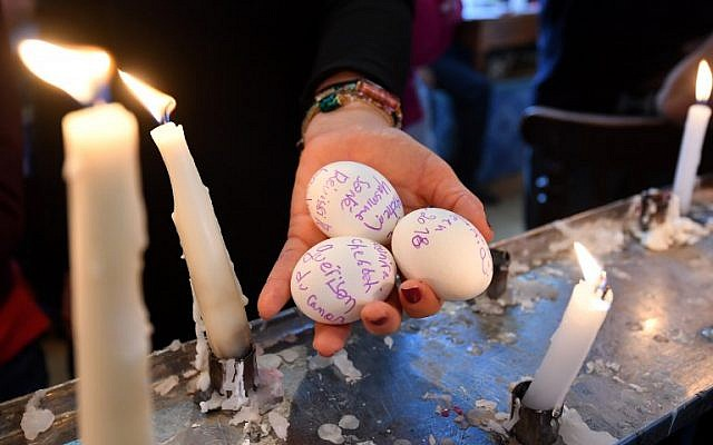 A French Jew holds eggs, on which she wrote her wishes, that will be placed in a cave under the Ghriba synagogue in Tunisia's Mediterranean resort island of Djerba on the first day of the annual Jewish pilgrimage to the synagogue May 2, 2018. (AFP / FETHI BELAID)