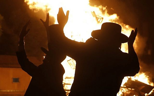 Ultra-Orthodox Jews dance around a bonfire in Jerusalem's Mea Shearim neighborhood on May 2, 2018, during celebrations for the Jewish holiday of Lag BaOmer. (AFP PHOTO / MENAHEM KAHANA)