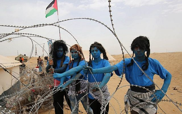 "Palestinians with their faces painted like characters from the movie ""Avatar"" pose for a picture ahead of the weekly ""March of Return"" clashes on the border between the Gaza Strip in Israel, east of Khan Younis in southern Gaza, on May 4, 2018. (AFP Photo/Said Khatib)"