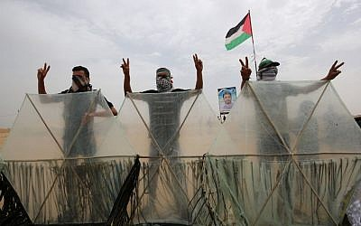 Palestinians pose behind kites before trying to fly them over the border fence with Israel, in Khan Younis in the southern Gaza Strip on May 4, 2018. Palestinians taking part in weekly clashes on the border have adopted a new tactic of attaching firebombs to kites to fly over the border fence into Israel. (AFP Photo/Said Khatib)