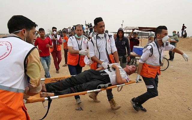 Palestinian paramedics carry a wounded man during a demonstration at the Israel-Gaza border, east of Khan Younis in the southern Gaza Strip, on May 4, 2018. (Said Khatib/AFP)