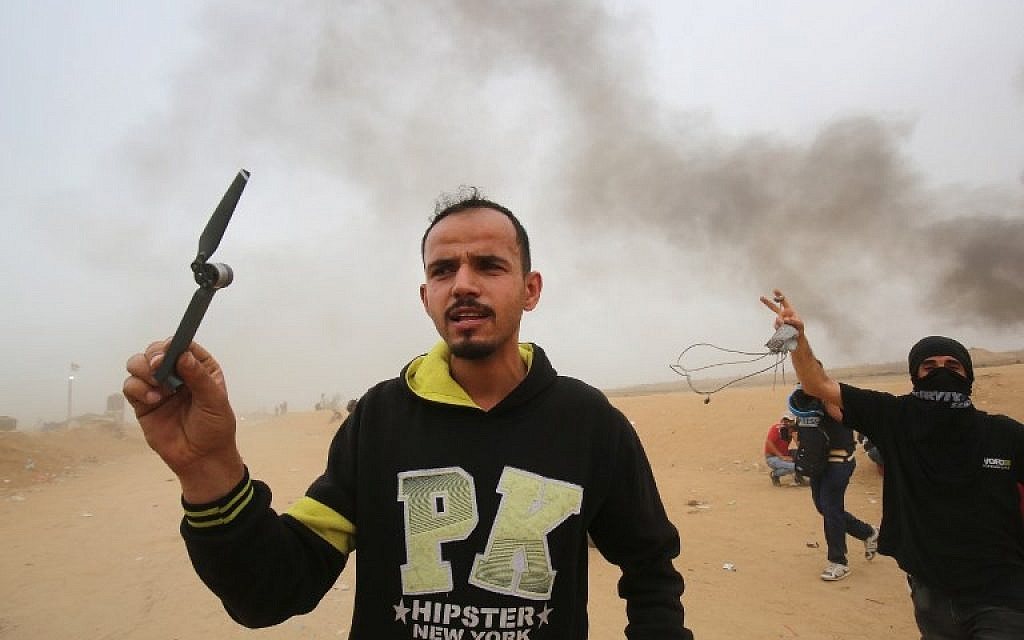A Palestinian holds what he says is a part of a propeller of an IDF army drone, east of Khan Younis in the southern Gaza Strip, on May 4, 2018. (Said Khatib/AFP)