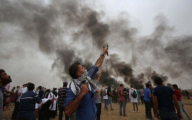 A Palestinian man uses a slingshot during weekly protests along the Gaza border near the city of Khan Younis on May 4, 2018. (Said Khatib/AFP)