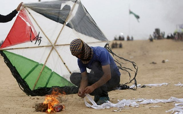 Illustrative: Palestinians prepare an incendiary device attached to a kite before trying to fly it over the border fence with Israel, on the eastern outskirts of Jabaliya, on May 4, 2018. (AFP Photo/Mohammed Abed)