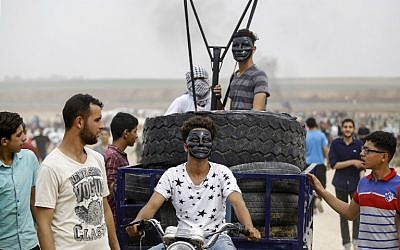 Palestinians ride in the back of a motorcycle cart carrying tires to be burned and a small catapult to hurl stones towards Israeli forces, during clashes near the border between the Gaza Strip and Israel, east of Jabaliya, on May 4, 2018. (AFP Photo/Mohammed Abed)