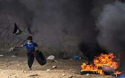 A Palestinian boy protester runs carrying a tire towards a fire during clashes with Israeli forces along the border with the Gaza strip east of Gaza City on May 4, 2018 (AFP PHOTO / MAHMUD HAMS)