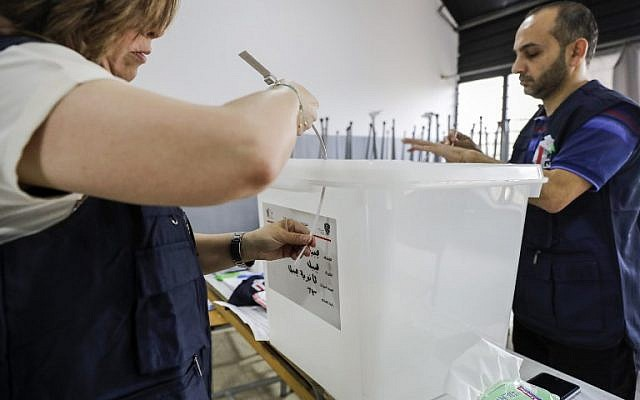 Lebanese election registrars break the seals open from a ballot box as their poll station opens to receive voters in the first parliamentary election in nine years, in the coastal city of Byblos, north of the capital Beirut, on May 6, 2018. (AFP/Joseph EID)