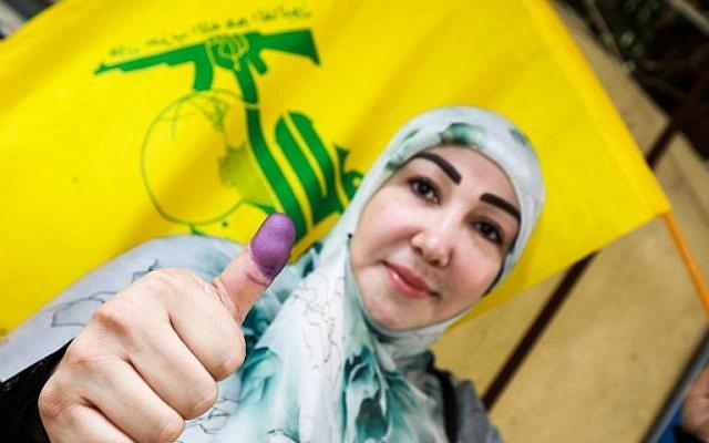Une femme chiite libanaise flashe son pouce taché d'encre et brandit un drapeau du Hezbollah après avoir voté à un bureau de vote dans la capitale Beyrouth le 6 mai 2018, alors que le pays vote lors des premières élections législatives en neuf ans.  (AFP PHOTO / ANWAR AMRO)