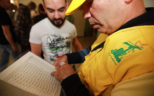 Un délégué du Hezbollah vérifie la liste des électeurs dans un bureau de vote dans la banlieue sud de Beyrouth le 6 mai 2018, alors que le pays vote lors des premières élections législatives en neuf ans.  Les bureaux de vote ont ouvert leurs portes à 7 heures du matin dans le petit pays, qui compte environ 3,7 millions d'électeurs, et devaient fermer 12 heures plus tard, les résultats des 15 districts étant attendus le jour suivant.  Le taux de participation sera crucial pour les chances d'un nouveau mouvement de la société civile de remporter une poignée de sièges, mais les analystes prédisent tous que les partis traditionnels sectaires maintiendront leur hégémonie.  / PHOTO AFP / ANWAR AMRO