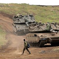 An Israeli soldier next to Merkava Mark IV tanks in the Golan Heights during a military drill on May 7, 2018. (AFP Photo/Jalaa Marey)