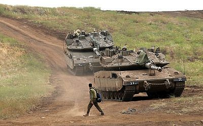 An Israeli soldier next to Merkava Mark IV tanks in the Golan Heights during a military drill on May 7, 2018. (AFP PHOTO / JALAA MAREY)