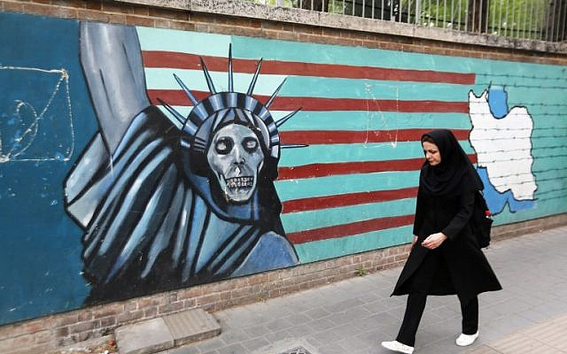 An Iranian woman walks past a mural on the wall of the former US embassy in the Iranian capital Tehran on May 8, 2018. (AFP / ATTA KENARE)
